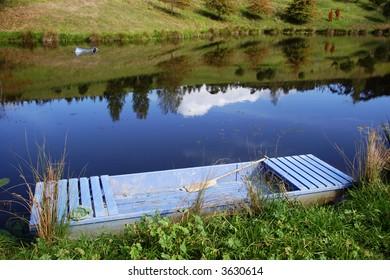 Old wooden boat on pond