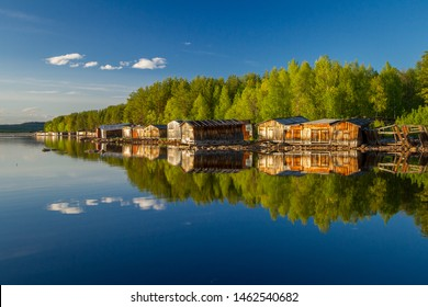Old wooden boat sheds on Lake Kovdozero in the Murmansk region, Zelenoborsky village near Kandalaksha. The reflection in the water of trees and boat garages