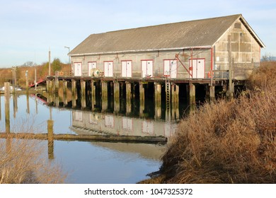 An old wooden boathouse used for storing fish equipment is raised on pylons above a small water inlet.