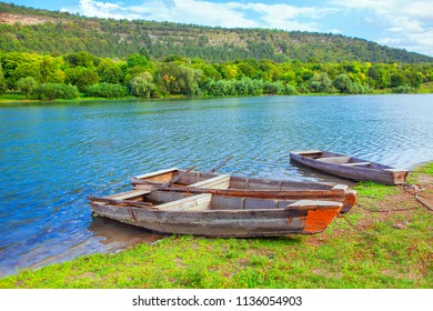 old wooden boats anchored on the river shore