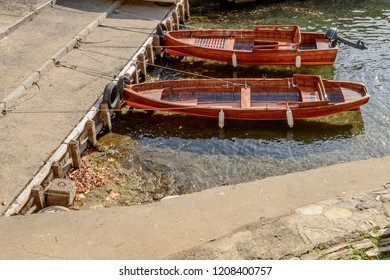 old wooden boats moored in harbor at historical touristic village on Como lake, shot in bright fall light at Moltrasio