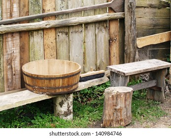 Old wooden bowl and bench against wooden fence, traditional wooden equipment.