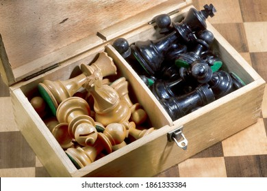 Old wooden box of wooden chess pieces.