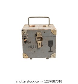 Old wooden box of gray color with a handle lock and iron corners. On the front side is a fragile load sign.