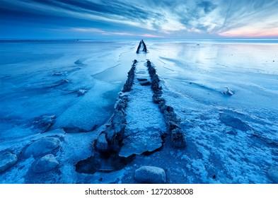 old wooden breakwater in frozen lake during dawn, Netherlands