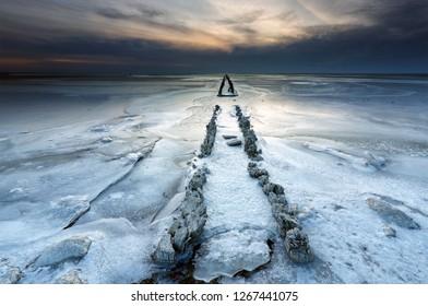 old wooden breakwater on frozen lake in winter