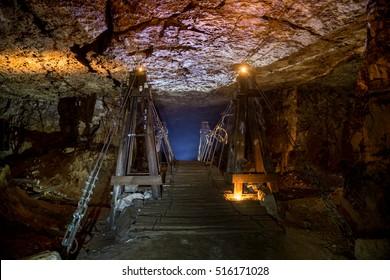 Old wooden bridge illuminated by candles in an abandoned limestone mine in Sock, Samara region