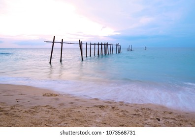 Old wooden bridge Lonely in the sea with sunset dramatic colorful tropical sea sky and cloud background and smooth wavy sea, Long exposure image, Romantic beach concept.