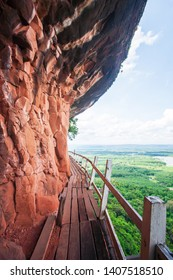 Old wooden bridge on edge of red sandstone cliff, agriculture field and blue sky in backgrounds. Bueng Kan, Thailand.