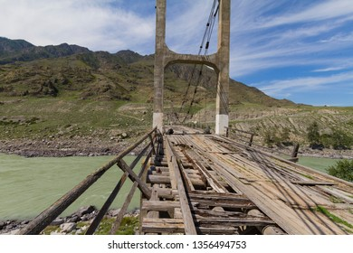 Old wooden Bridge on  iron ropes through the Katun River. Summer sunny time. Close up.
