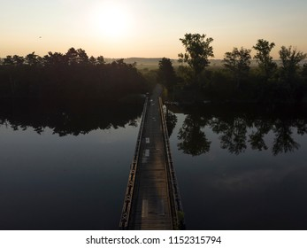 Old wooden bridge with rails over river against sunset background. Tisa River in Vojvodina region, Serbia.
