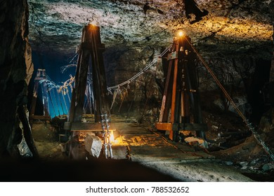 Old wooden bridge in scary abandoned underground limestone mine cave or tunnel or dark corridor with mysterious illumination in Samara region, Russia, toned