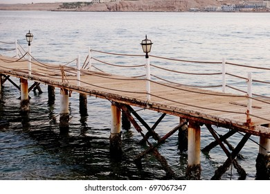 The old wooden bridge to the sea in evening time.