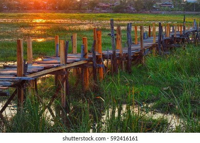 Old wooden bridge under evening sunlight whit flare light.