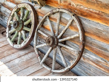Old wooden broken wagon wheels in the abandoned village in summer day