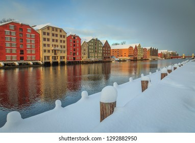 Old wooden buildings, magazines, by the shores of Nidelva river, winter time in Trondheim, Norway.