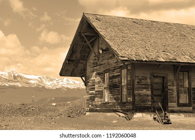Old wooden cabin in field with mountain background in rural setting with sepia toning