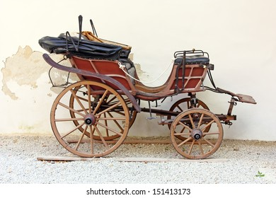 Old wooden carriage in front of wall