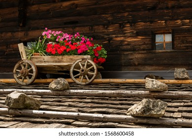 An old wooden cart with beautiful flowers on the roof of an old house (South Tyrol, Italy)