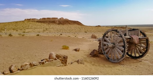 Old wooden cart with giant wheels abandoned in the desert along the Great Silk Road