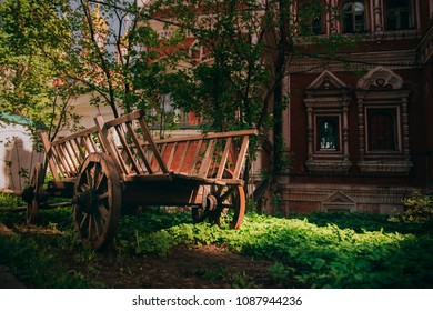 old wooden cart on the background of a brick house and church