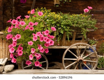 An old wooden cart overflowing with pink petunias and other colorful flowers