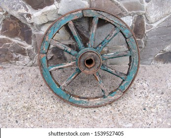An old wooden cartwheel with a broken spoke. Cracked wooden elements painted with blue paint. Leaning against a stone wall. Close-up. Selective focus. Copy space.