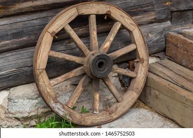 Old wooden cartwheel on logs background