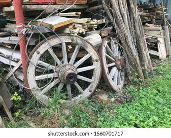 Old wooden cartwheel wheels among agricultural implements on a farm.