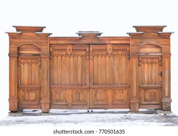 Old wooden carved gates covered with snow