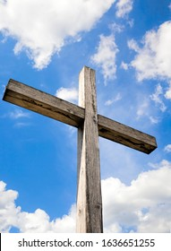 old wooden Catholic cross against blue sky and white clouds in Sunny weather, closeup of religious symbols