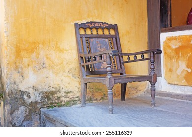 old wooden chair against a background of yellow wall, Vietnam, Hoi An