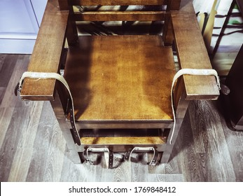Old wooden chair with shabby leather straps attached to the armrests and legs. Chair for torture. Antique electric chair. Museum exhibit. Noise, film grain