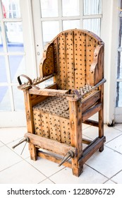 old wooden chair with spikes for torture