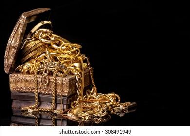 Alte Holztruhe mit Haufen verschiedener goldener Schmuckstücke einzeln auf schwarzem Hintergrund.