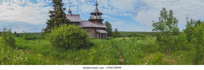 Old wooden church among the overgrown field. rural panoramic landscape
