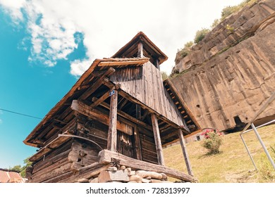 old wooden church carved in stone. the monastery is at the foot of the mountain