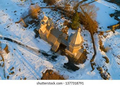 The old wooden church of Dmitry Solunsky of the Myrrh-stream (1783) on April evening (shooting from a quadrocopter). Village Shcheleyki, Leningrad Region, Russia