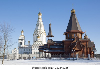 An old wooden church on the background of a new white-stone Cathedral of all the Saints with golden domes.Minsk.Belarus.