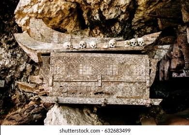 Old wooden coffin with skulls and bones nearby on a rock. Hanging coffins, graves. Traditional burials site, cemetery Kete Kesu in Rantepao, Tana Toraja, Sulawesi, Indonesia.