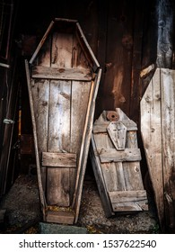 Old wooden coffins for adult and child leaning up in a shed.