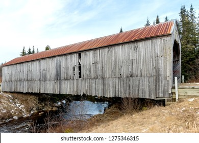An old wooden covered bridge in Lepreau, New Brunswick, Canada. The bridge is no longer in use.