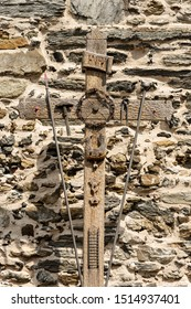 Old wooden cross with the symbols of the Passion of Christ, pincer, ladder, hammer, chalice, spear, crown of thorns, rooster, nails and text INRI. Vernazza village, Italy