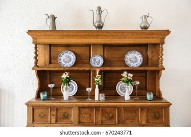 Old wooden cupboard served with flowers, plates and candles.