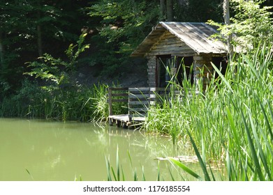 Old wooden dark house for waterfowl on the shore of a forest lake in the reserve