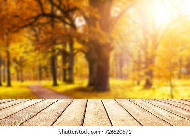 Old wooden desk top with golden leaves, autumn background