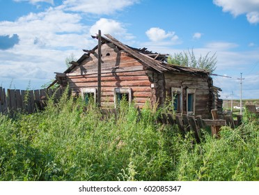 Old wooden dilapidated rural house stands in a thicket of bushes and grass. Abandoned building.