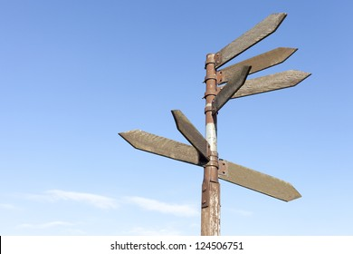 Old wooden direction signs against blue sky