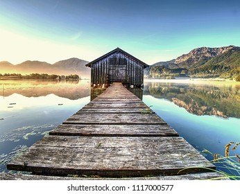 Old wooden dock houses on the lake with typical wooden pier,  the Walchensee in Bavaria Germany