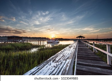 Old wooden dock leading to a beautiful sunrise over the marsh in Savannah, Georgia, USA